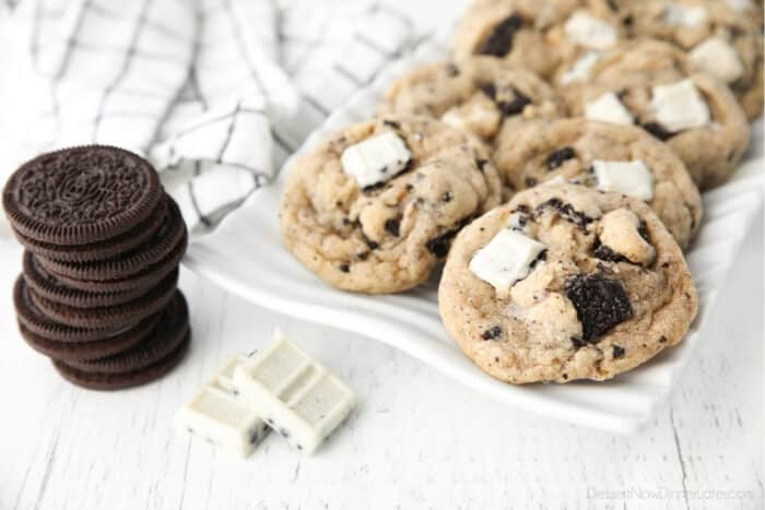 Plate of cookies and cream cookies with a stack of Oreos and a broken up cookie & cream candy bar on the side.