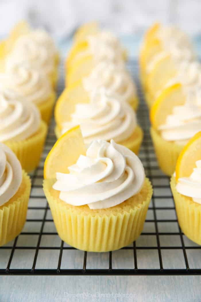 Cream cheese frosting with a lemon wedge on top of lemon cupcakes.