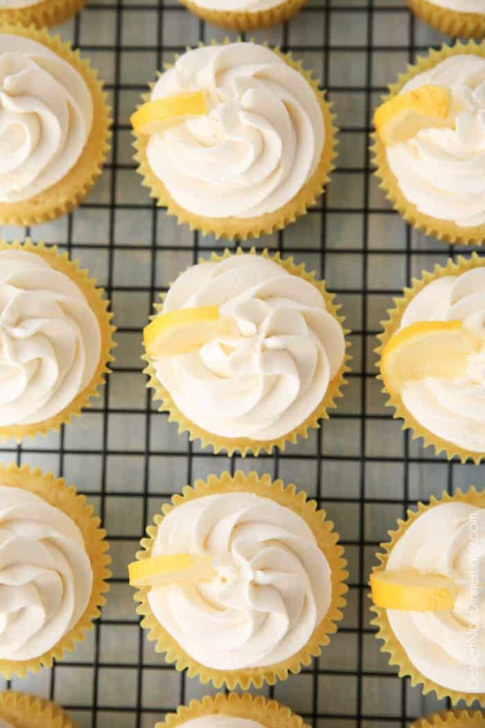 Top view of cream cheese frosting and lemon wedges atop lemon cupcakes.