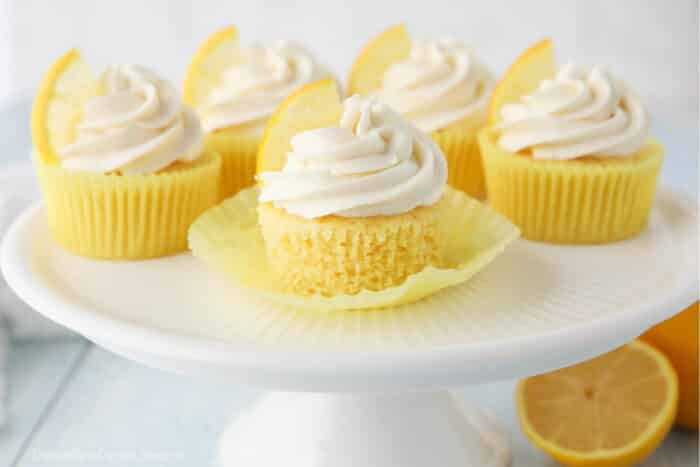 Cake plate full of lemon cupcakes with cream cheese frosting.