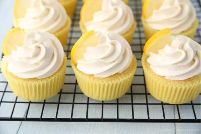 Cooling rack full of frosted lemon cupcakes.