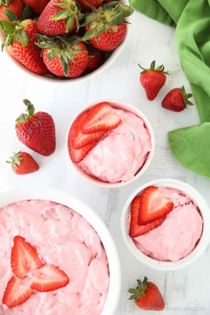Top view of three bowls of strawberry fluff with sliced strawberries on top.