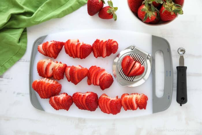 Cutting board full of strawberries that have been sliced with an egg slicer.