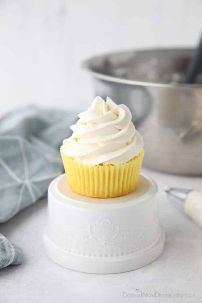 Focus is on a cupcake piled high with whipped cream cheese frosting.
