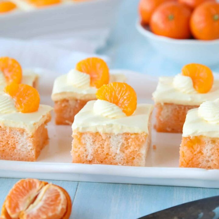 Slices of Orange Creamsicle Cake on a plate with mandarin orange slices on top.