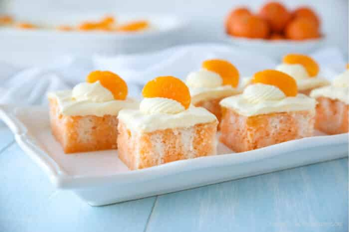 Marbled orange cake on plate with vanilla frosting and a mandarin orange slice on each piece.
