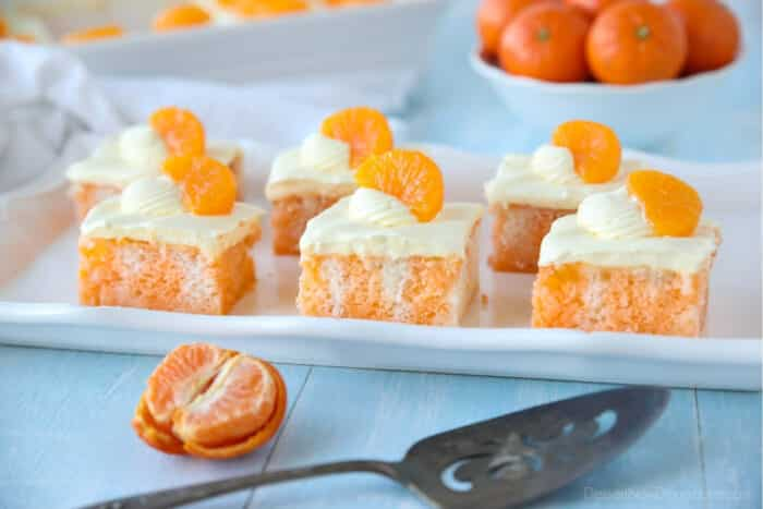 Slices of Orange Creamsicle Cake on a plate with mandarin oranges.