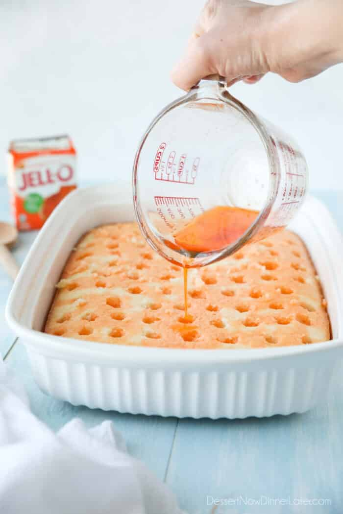 Pouring orange jello into holes of white cake.