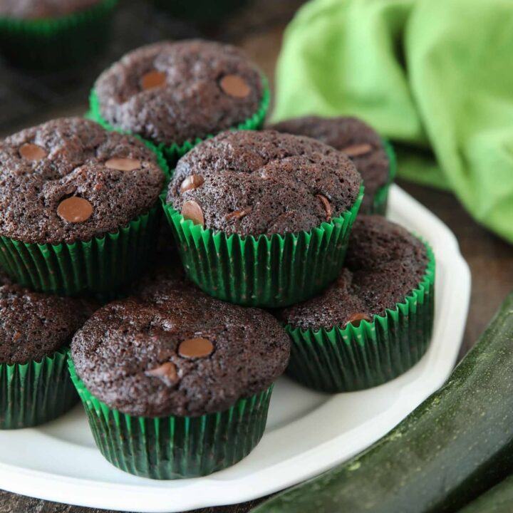 Plate full of chocolate zucchini muffins with chocolate chips.