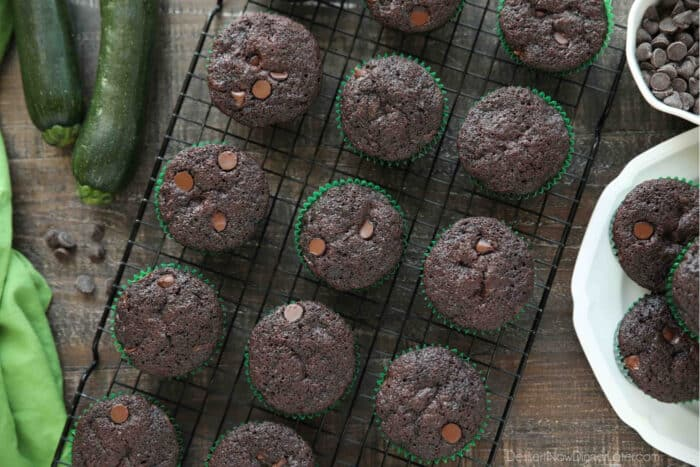 Top view of cooling rack with chocolate zucchini muffins with chocolate chips inside.