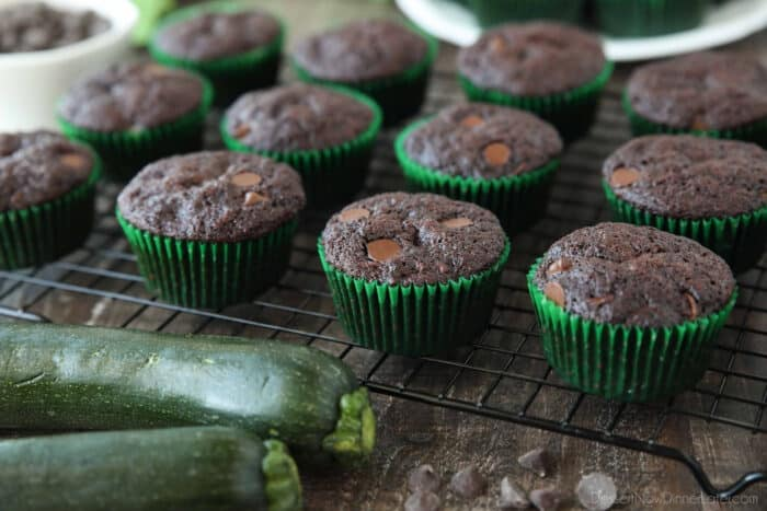 Side view of cooling rack with chocolate zucchini muffins in green paper wrappers.
