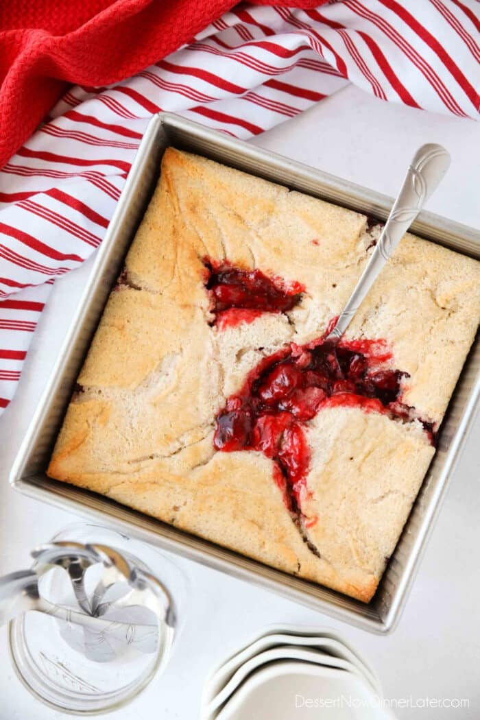 Cherry Cobbler in a square baking pan with a spoon revealing cherry pie filling underneath the cake.