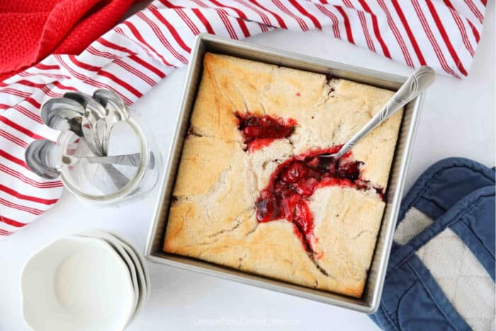 Top view of cherry cobbler in a square baking dish with a serving spoon.