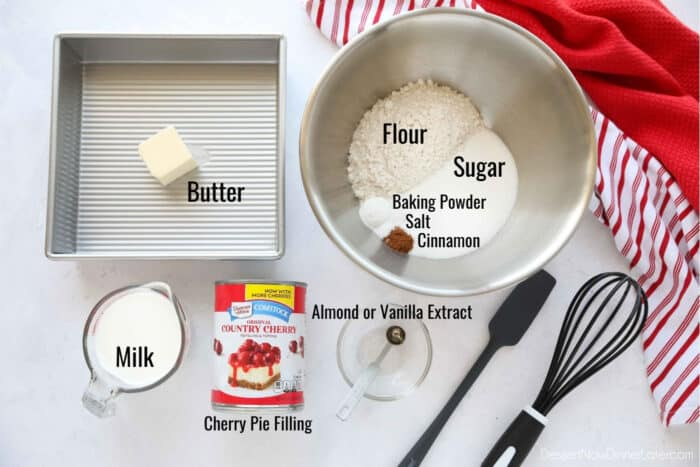 Ingredients for easy cherry cobbler: Butter, flour, sugar, baking powder, salt, cinnamon, milk, almond or vanilla extract, and cherry pie filling.