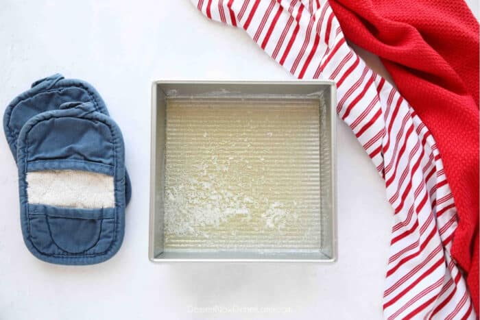 Melted butter in a square baking dish.