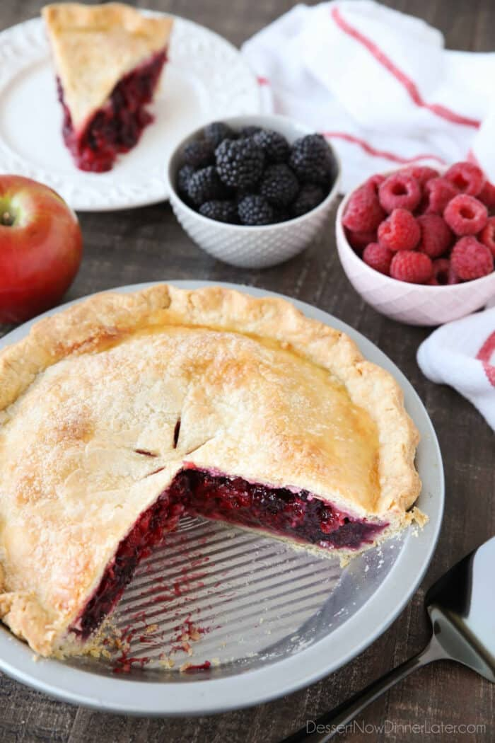 Razzleberry Pie in the pan with a slice on a plate in the background.