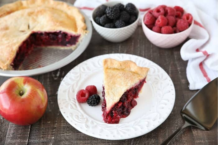 Slice of razzleberry pie on plate with raspberries and blackberries.
