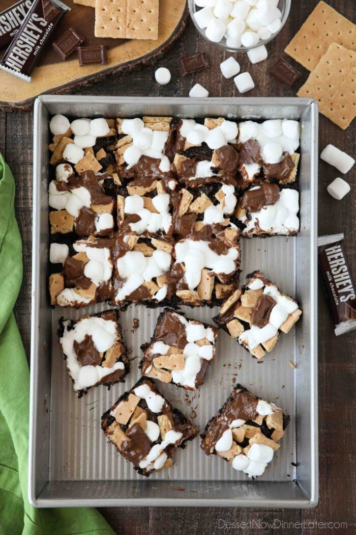 S'mores Brownies with graham crackers, mini marshmallows, and Hershey's chocolate bars in a pan, cut into squares with a few missing, and other brownies separated from the rest.