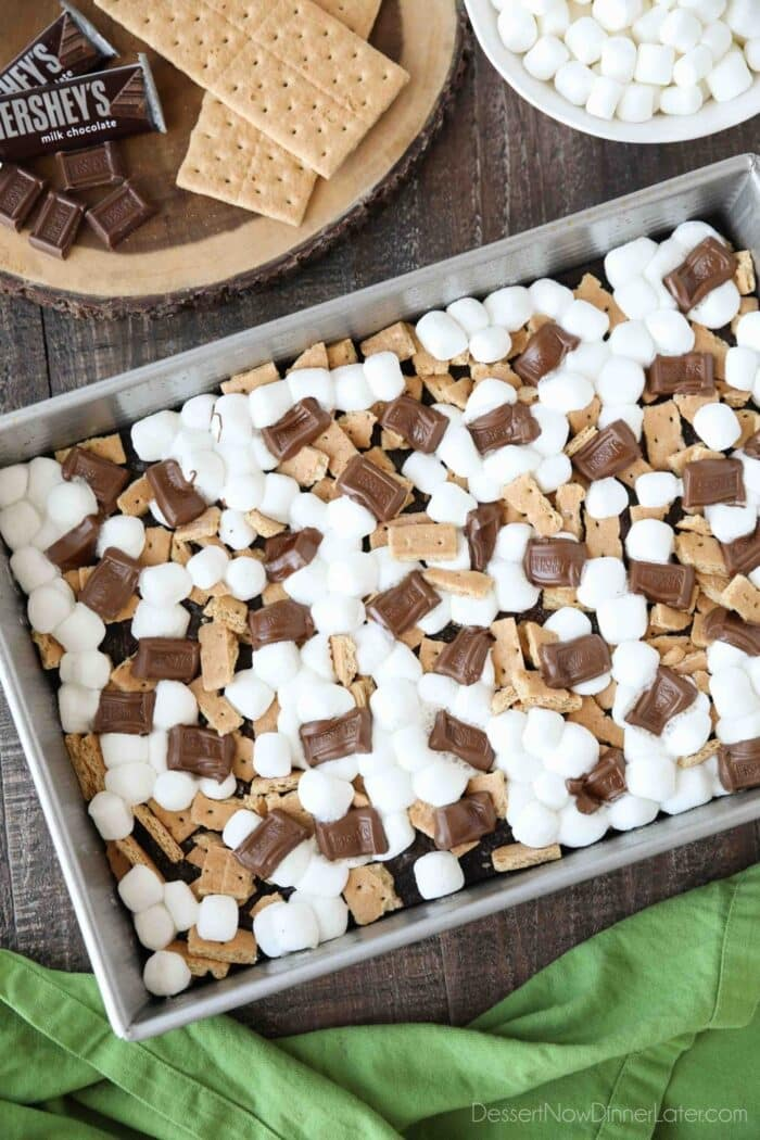 Top view of melted marshmallows and chocolate bars with graham cracker pieces on top of baked brownies.