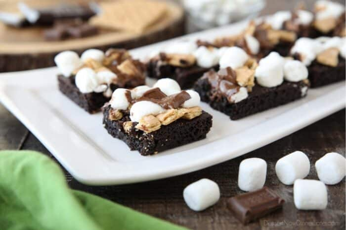 Close up side view of dark chocolate brownies topped with smores ingredients: graham crackers, marshmallows, and chocolate.