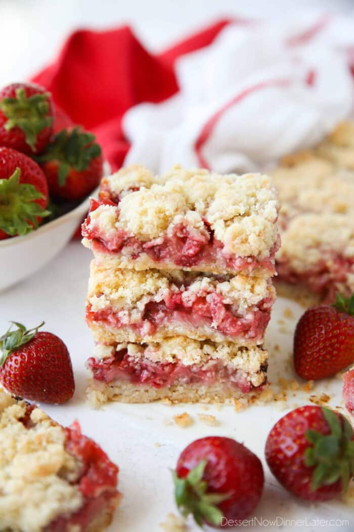 Three strawberry crumb bars stacked on top of each other surrounded by fresh whole strawberries.