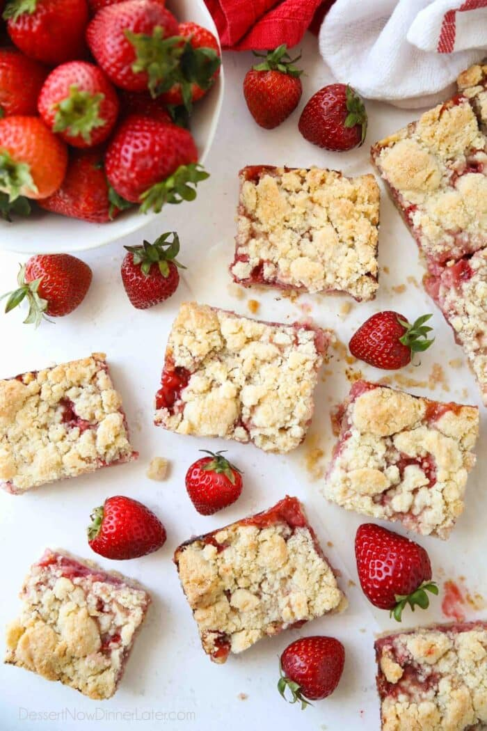 Strawberry Crumb Bars cut into squares with fresh strawberries.