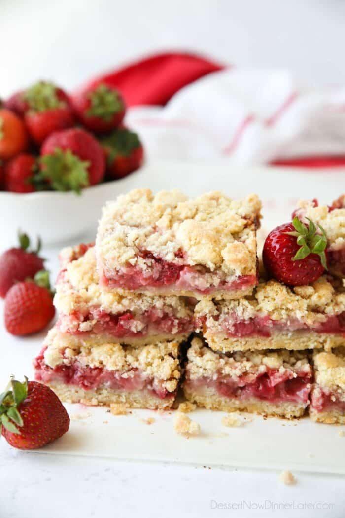 Stack of strawberry crumb bars with fresh strawberries.