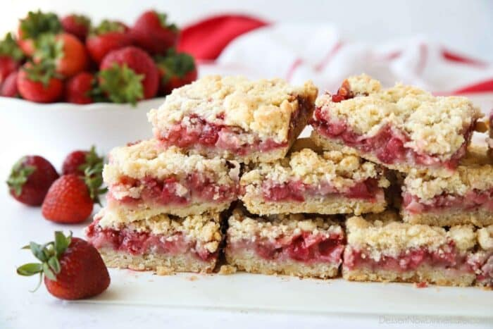 Strawberry Crumb Bars stacked on top of parchment paper.