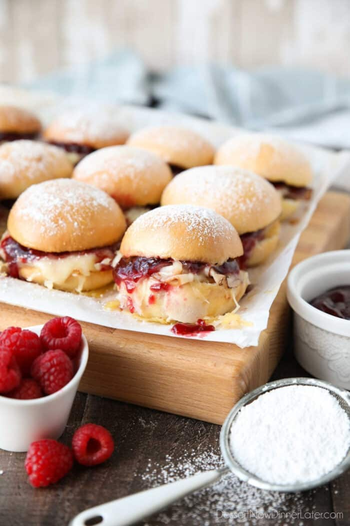 Monte Cristo Sliders on parchment paper with ham, turkey, Swiss cheese, and raspberry preserves inside of dinner rolls with powdered sugar on top.