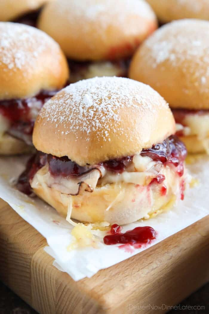 Close up of ham, turkey, and Swiss cheese mini sandwiches with raspberry preserves.