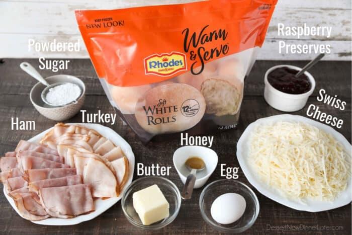 Ingredients for Monte Cristo Sliders: dinner rolls, ham, turkey, Swiss cheese, raspberry preserves, butter, honey, egg, and powdered sugar.