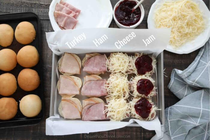 Assembling Monte Cristo Sliders: Cut rolls in half. Place bottom half in a prepared baking dish. Layer turkey, ham, cheese, and jam.