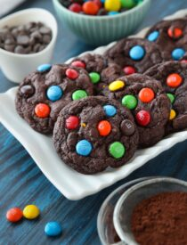 Chocolate cookies on a plate made with cocoa powder, chocolate chips and M&M's.