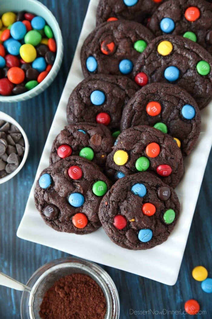 Serving platter of chocolate cookies with M&M's and chocolate chips inside.