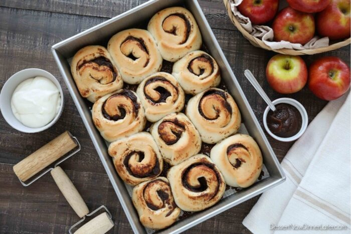 Baked Apple Butter Cinnamon Rolls in Pan with cream cheese glaze in a bowl on the side.