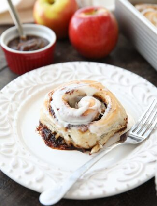 Apple Butter Cinnamon Roll on plate with a fork.