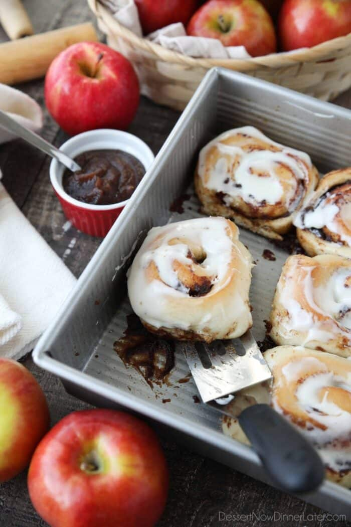 Scooping an apple butter cinnamon roll out of the pan with a spatula.