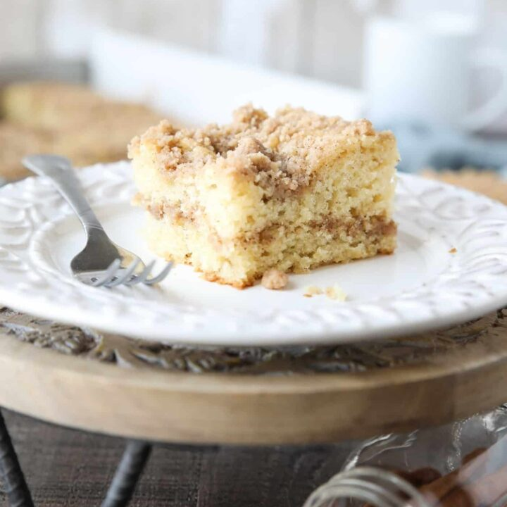 Close up of a slice of sour cream coffee cake on a plate with a line of cinnamon streusel in the center of the cake and more streusel on top.