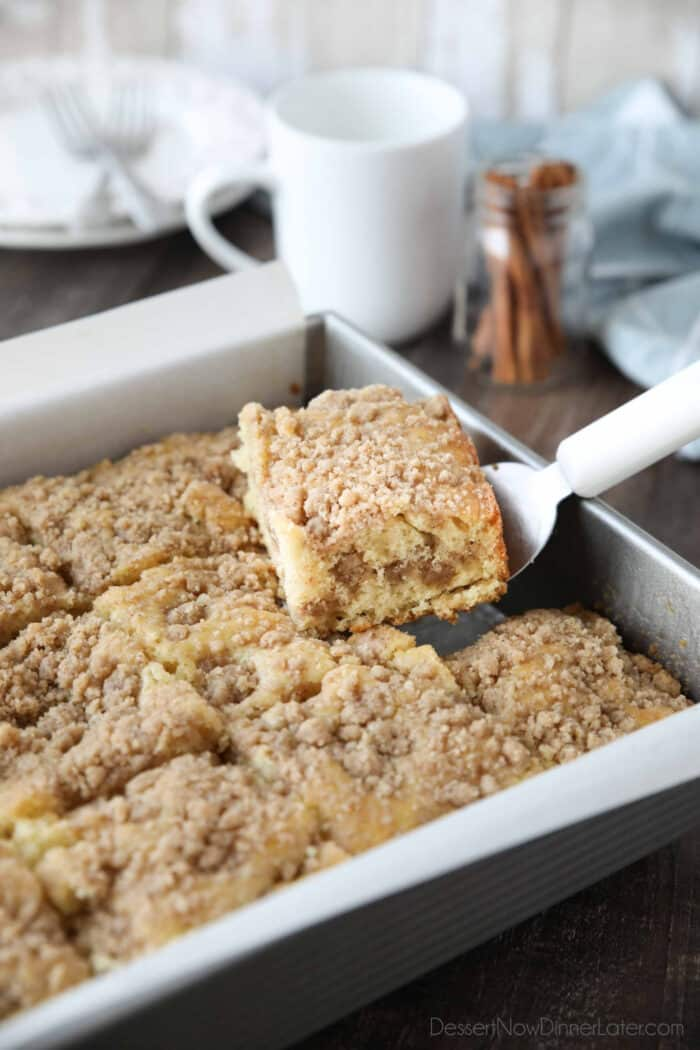 Scooping a piece of sour cream coffee cake out of the pan.