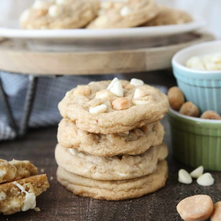Stacked White Chocolate Macadamia Nut Cookies with extra nuts and white chocolate chips on the side.