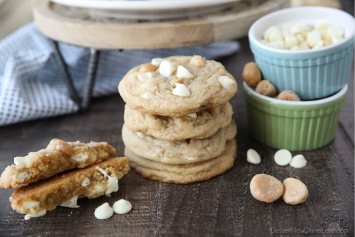 Stack of White Chocolate Macadamia Nut Cookies with one cookie broken in half to show the soft center with melted white chocolate chips.