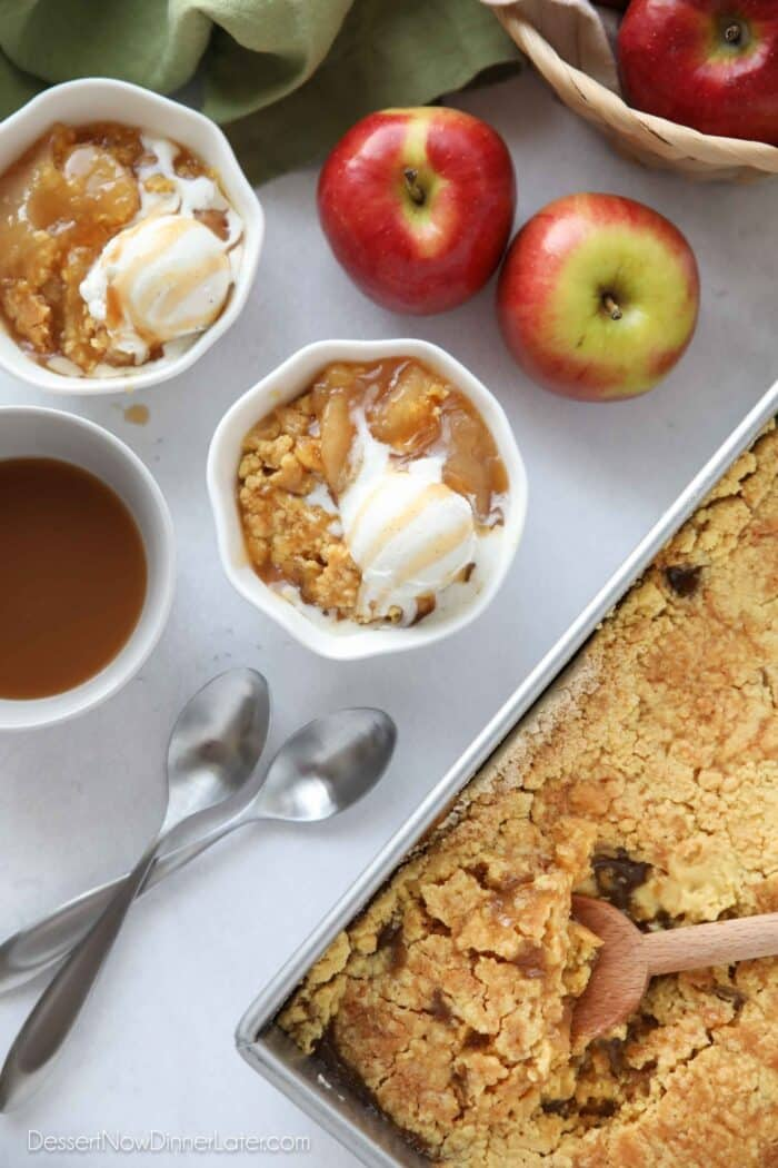 Top view of two bowls of apple cobbler with caramel sauce and ice cream melting on top.