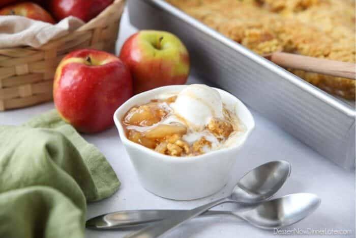 Close up side view of bowl full of caramel apple dump cake and vanilla ice cream.