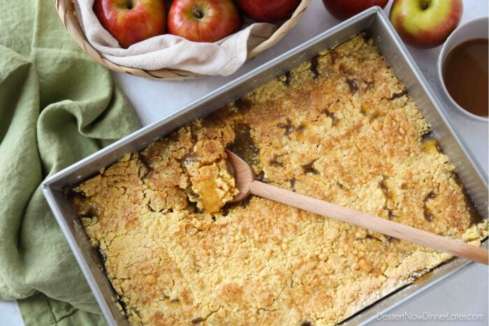 Baking pan with a spoon scooping up some caramel apple dump cake.