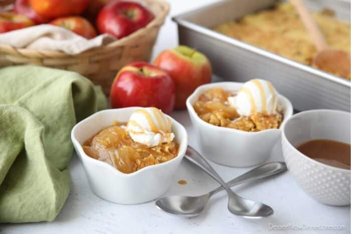Caramel apple dump cake served up in small bowls with vanilla ice cream and caramel on top.