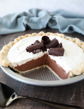 Angled view of Chocolate Cream Pie with a couple pieces taken out of the pan.