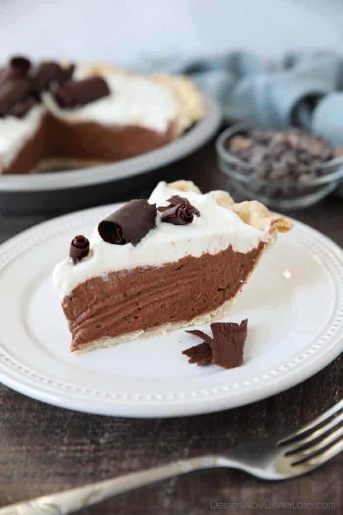Slice of pie on a plate with a flaky pastry crust layered with chocolate pudding filling, whipped cream, and chocolate curls on top.