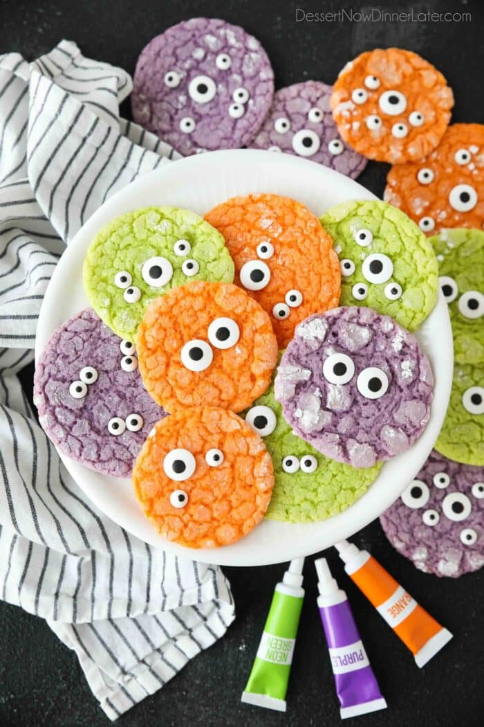 Bright colored Halloween cookies on a plate with powdered sugar cracks and candy eyeballs.
