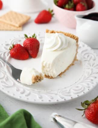 Slice of no bake cheesecake on a plate with a fork full.