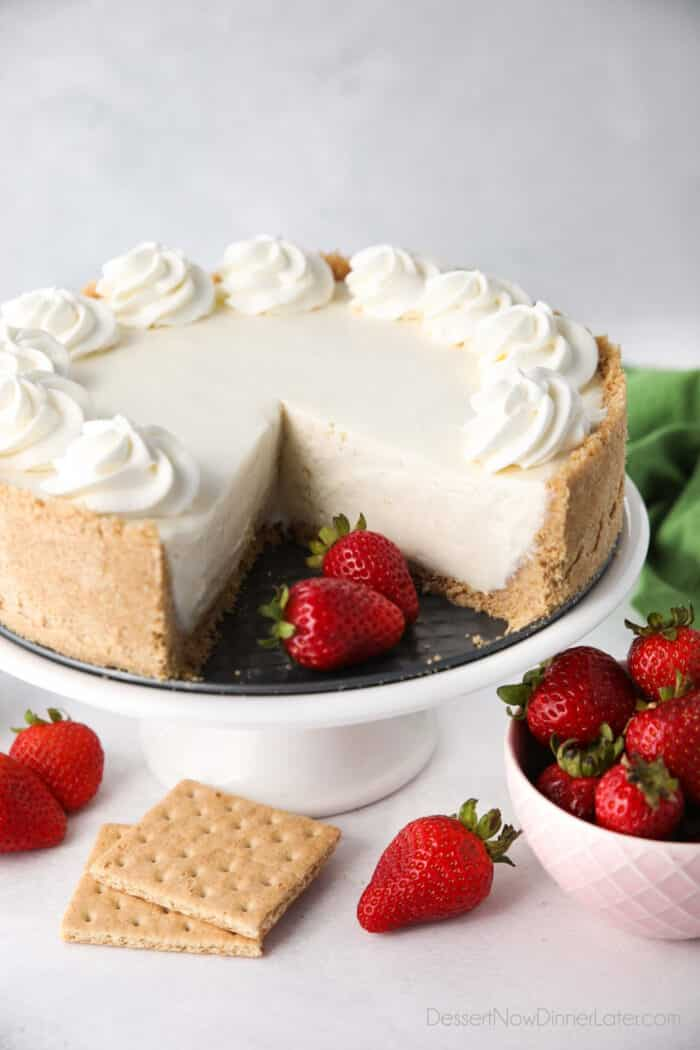 No bake cheesecake on a cake plate with a couple slices taken out and fresh strawberries on the side.